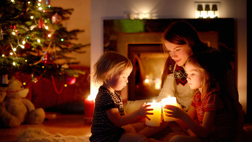 Family in front of Christmas tree, candles